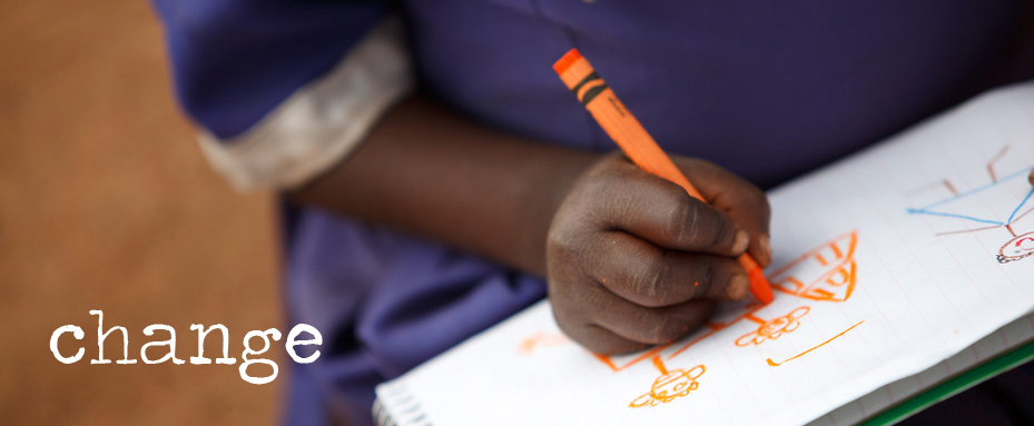 African student writing on paper with orange crayon. Photo credit: Jacquie Labatt