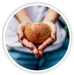 Circle image with someone holding an apple in their hands