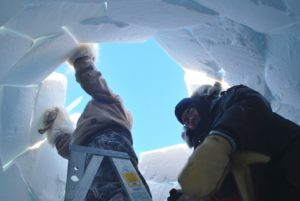 Two men inserting the final blocks of snow into the roof of an iglu