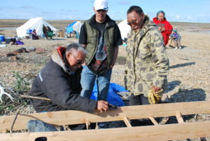 One man sitting behind a sled teaching two men who stand above him how to build the frame