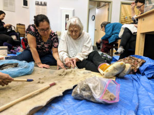 Two women sitting on the ground on top of a blue tarp learning how to dehair a bearded seal skin