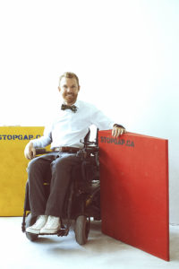 Full body shot of Luke Anderson, Founder and Executive Director of StopGap Foundation in his wheelchair in front of accessibility ramps with the STOPGAP.CA logo