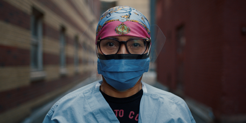 A women in scrubs and a face mask and glasses