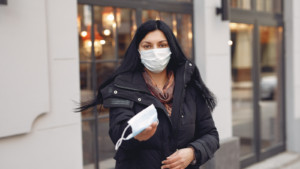 Woman wearing a mask with an outstretched hand holding out a mask to the camera man.