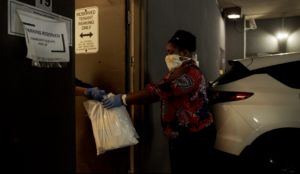 Woman wearing a mask handing off bags of groceries in a parking garage.