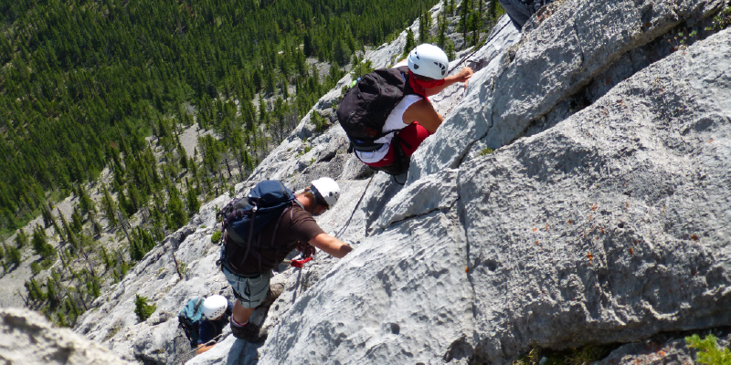 A line of hikers climbing up a steep rock mountain