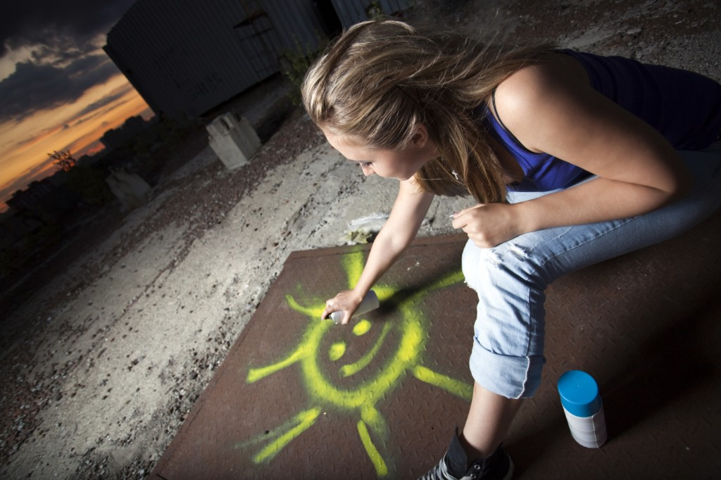 Young woman painting the sun at sunset