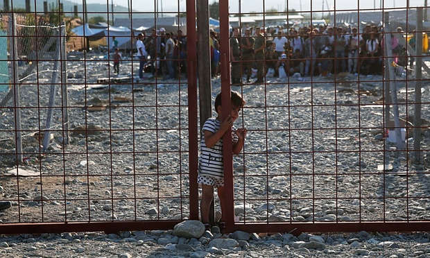 Un jeune garçon se glisse dans une étroite ouverture d'une barrière érigée à l'intérieur d'un camp de réfugiés en Macédoine. Photograph: Win McNamee / Getty Images